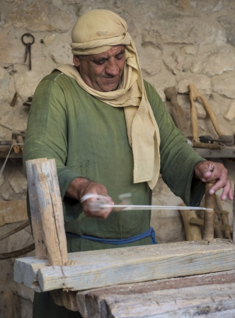 NAZARETH, ISRAEL - OCT 15 : Palestinian carpenter work with traditional tools in October 15 2012 at Nazareth Village, historical re-creation of Nazareth as it was at the time of Christ Stock Photo - 16994299
