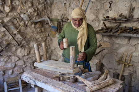 crist: NAZARETH, ISRAEL - OCT 15 : Palestinian carpenter work with traditional tools in October 15 2012 at Nazareth Village, historical re-creation of Nazareth as it was at the time of Christ