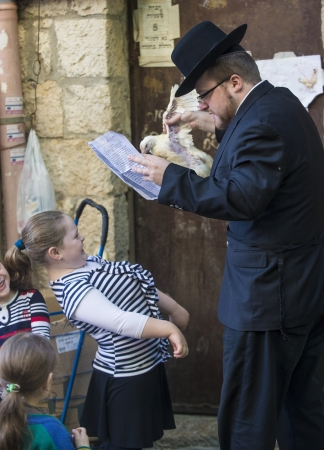 kippa: JERUSALEM - SEP 25 : An ultra Orthodox Jewish man waves a chicken over his childs heads during the Kaparot ceremony held in Jerusalem Israel in September 25 2012