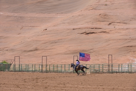 GALLUP , NEW MEXICO - AUGUST 10 : Cowgirl with American flag at the Opening Ceremony of the 92nd annual Indian Rodeo in Gallup, NM on August 10 2013