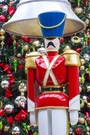 close up on a wooden nutcracker with a background of christmas tree and ornaments photo