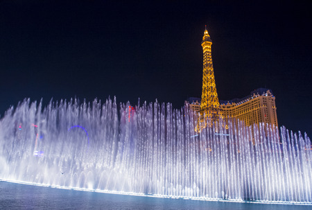 bellagio fountains: LAS VEGAS - MARCH 10 : Night view of the dancing fountains of Bellagio and the Eiffel Tower replica of Paris Las Vegas Resort in Las Vegas Nevada, USA on March 10 , 2014