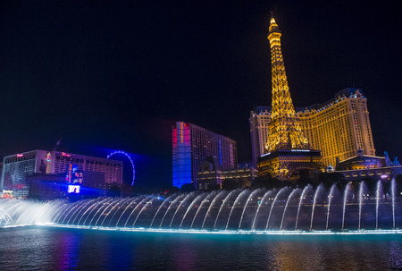 LAS VEGAS - MARCH 10 : Night view of the dancing fountains of Bellagio and the Eiffel Tower replica of Paris Las Vegas Resort in Las Vegas Nevada, USA on March 10 , 2014