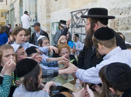 chassidim: GERUSALEMME - APRIL 05: Un Ultra uomo Ebreo ortodosso distribuendo cibo ai bambini poveri a Gerusalemme Israele il 5 aprile 2012 fornendo cibo ai poveri � uno dei costumi di Pasqua
