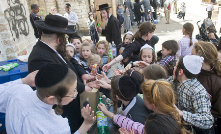 hasidim: JERUSALEM - APRIL 05 : An Ultra Orthodox Jew man handing out food to poor children in Jerusalem Israel on April 05 2012 providing food to the poor is one of the customs of Passover