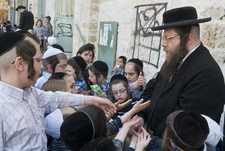 ni�os pobres: JERUSAL�N - 05 de abril: Un hombre ultra ortodoxa Judio repartiendo alimentos a los ni�os pobres en Jerusal�n Israel el 05 de abril 2012 el suministro de alimentos a los pobres es una de las costumbres de la Pascua