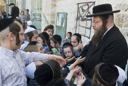 shearim: JERUSALEM - APRIL 05 : An Ultra Orthodox Jew man handing out food to poor children in Jerusalem Israel on April 05 2012 providing food to the poor is one of the customs of Passover