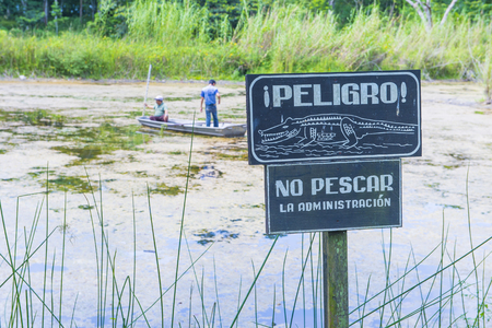 rainwater: TIKAL , GUATEMALA - JULY 29 : Crocodile warning sign near an artificial pond in Tikal Guatemalas national park on July 29 2015 The pond was created by the Mayans For collecting rainwater Editorial