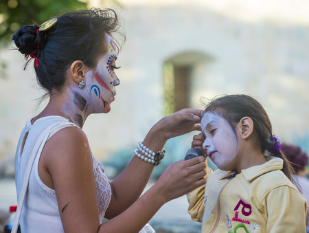face covered: OAXACA , MEXICO - NOV 02 : Unidentified participant has his face covered with makeup on a carnival of the Day of the Dead in Oaxaca, Mexico on November 02 2015. Editorial