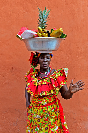 colombian food: CARTAGENA , COLOMBIA - FEB 04 : Palenquera woman sell fruts in Cartagena ,Colombia on Februery 04 2016. Palenqueras are a unique African descendat ethnic group found in the north region of South America