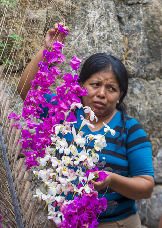el salvadoran: PANCHIMALCO , EL SALVADOR - MAY 08 : A Salvadoran woman decorates palm fronds with flowers during the Flower & Palm Festival in Panchimalco, El Salvador on May 08 2016 Editorial