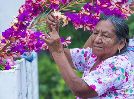 cristian: PANCHIMALCO , EL SALVADOR - MAY 08 : A Salvadoran woman decorates palm fronds with flowers during the Flower & Palm Festival in Panchimalco, El Salvador on May 08 2016 Editorial