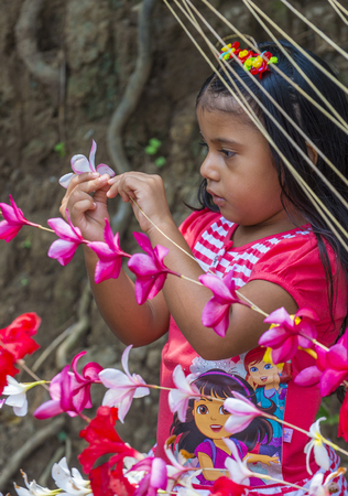 cristian: PANCHIMALCO , EL SALVADOR - MAY 08 : A Salvadoran girl decorates palm fronds with flowers during the Flower & Palm Festival in Panchimalco, El Salvador on May 08 2016 Editorial