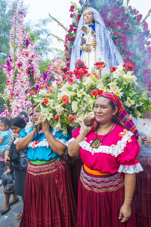 el salvadoran: PANCHIMALCO , EL SALVADOR - MAY 08 : Salvadoran woman carry an altar with a statue of Virgin Mary during the procession of the Flower & Palm Festival in Panchimalco, El Salvador on May 08 2016