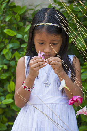 PANCHIMALCO , EL SALVADOR - MAY 08 : A Salvadoran girl decorates palm fronds with flowers during the Flower & Palm Festival in Panchimalco, El Salvador on May 08 2016 Editorial