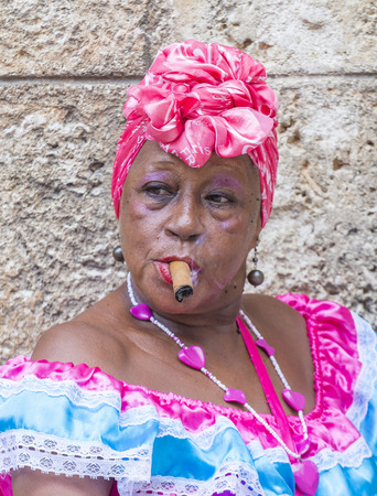 18 year old: HAVANA, CUBA - JULY 18 : A portrait of a Cuban woman smoking cigar in old Havana street on July 18 2016. Cuba now exports more than 90 million cigars a year