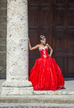 HAVANA, CUBA - JULY 18 : Cuban woman with red dress in old Havana street on July 18 2016. The historic center of Havana is UNESCO World Heritage Site since 1982.