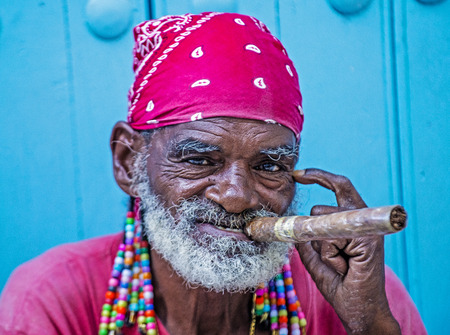 hombre fumando puro: HAVANA, CUBA - JULY 18 : A portrait of a Cuban man smoking cigar in old Havana street on July 18 2016. Cuba now exports more than 90 million cigars a year