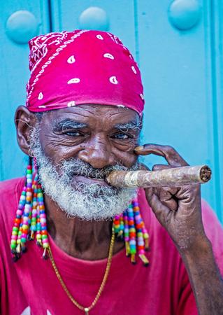 hombre fumando puro: HAVANA, CUBA - JULY 18 : A portrait of a Cuban man smoking cigar in old Havana street on July 18 2016. Cuba now exports more than 90 million cigars a year