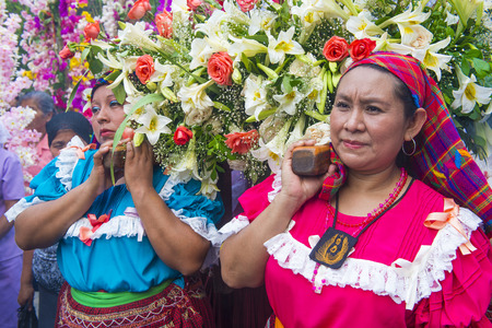 PANCHIMALCO , EL SALVADOR - MAY 08 : Salvadoran woman carry an altar with a statue of Virgin Mary during the procession of the Flower & Palm Festival in Panchimalco, El Salvador on May 08 2016