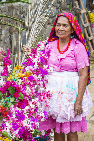 PANCHIMALCO , EL SALVADOR - MAY 08 : A Salvadoran woman decorates palm fronds with flowers during the Flower & Palm Festival in Panchimalco, El Salvador on May 08 2016 Editorial