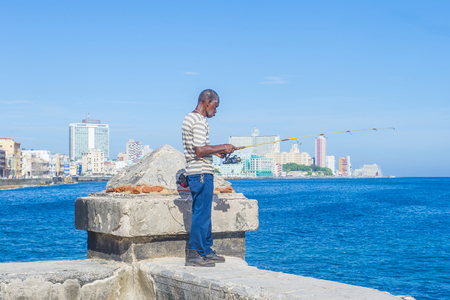 street rod: HAVANA, CUBA - JULY 18 : Cuban fisherman at the seafront wall of the Malecon in Havana on July 18 2016. The historic center of Havana is UNESCO World Heritage Site since 1982.