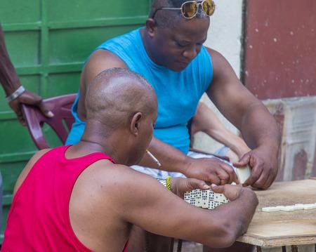 play popular: HAVANA, CUBA - JULY 18 : Unidentified men play dominos on the street on July 18 2016 in Havana , Cuba. Domino is one of the most popular games in Cuba Editorial