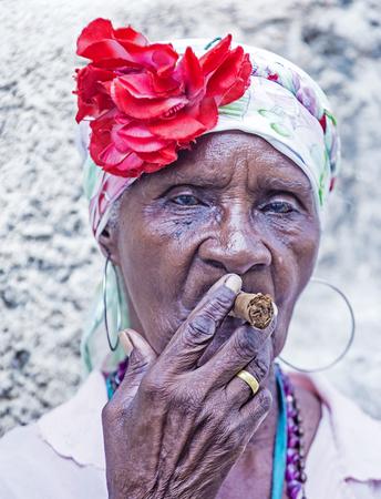 HAVANA, CUBA - JULY 18 : A portrait of a Cuban woman smoking cigar in old Havana street on July 18 2016. Cuba now exports more than 90 million cigars a year
