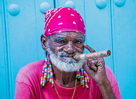 18 year old: HAVANA, CUBA - JULY 18 : A portrait of a Cuban man smoking cigar in old Havana street on July 18 2016. Cuba now exports more than 90 million cigars a year