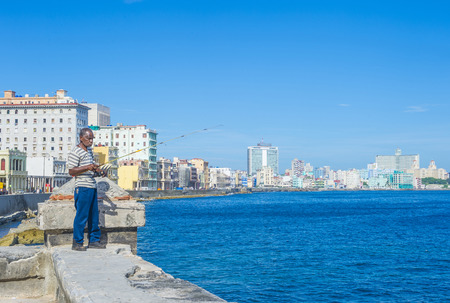 HAVANA, CUBA - JULY 18 : Cuban fisherman at the seafront wall of the Malecon in Havana on July 18 2016. The historic center of Havana is UNESCO World Heritage Site since 1982.