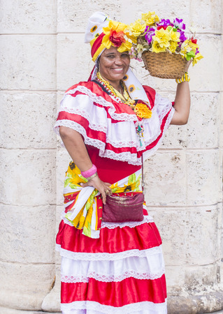 adobe wall: HAVANA, CUBA - JULY 18 : Cuban women with traditional clothing in old Havana street on July 18 2016. The historic center of Havana is UNESCO World Heritage Site since 1982.