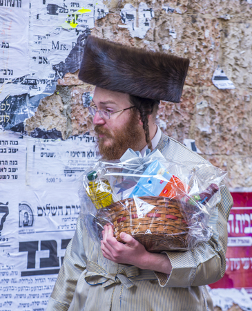 hasidic: JERUSALEM - MARCH 13 : Ultra Orthodox man holding Mishloach Manot during Purim in Mea Shearim Jerusalem on March 13 2017 , Mishloach Manot is traditional food gifts given during Purim Editorial