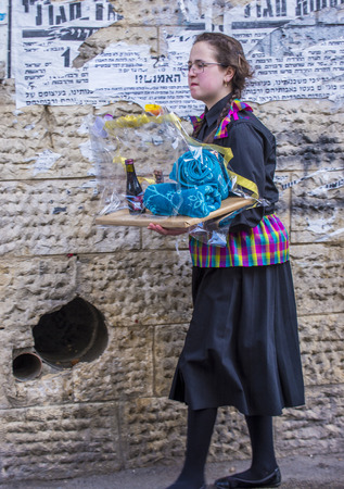 shearim: JERUSALEM - MARCH 13 : Ultra Orthodox woman holding Mishloach Manot during Purim in Mea Shearim Jerusalem on March 13 2017 , Mishloach Manot is traditional food gifts given during Purim Editorial