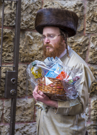 shearim: JERUSALEM - MARCH 13 : Ultra Orthodox man holding Mishloach Manot during Purim in Mea Shearim Jerusalem on March 13 2017 , Mishloach Manot is traditional food gifts given during Purim Editorial
