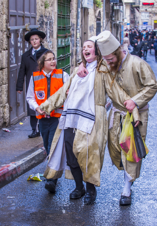 hasidic: JERUSALEM - MARCH 13 : Ultra Orthodox drunk boys during Purim in Mea Shearim Jerusalem on March 13 2017 , Purim is a Jewish holiday celebrates the salvation of the jews from genocide in ancient Persia Editorial