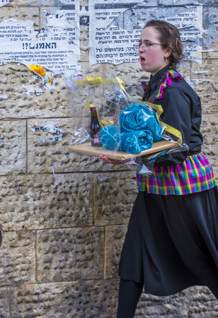 mea: JERUSALEM - MARCH 13 : Ultra Orthodox woman holding Mishloach Manot during Purim in Mea Shearim Jerusalem on March 13 2017 , Mishloach Manot is traditional food gifts given during Purim Editorial