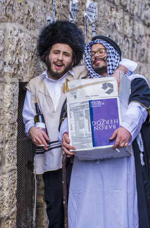 JERUSALEM - MARCH 13 : Ultra Orthodox men holding Mishloach Manot during Purim in Mea Shearim Jerusalem on March 13 2017 , Mishloach Manot is traditional food gifts given during Purim