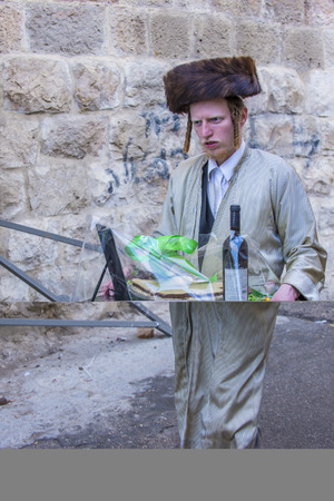 JERUSALEM - MARCH 13 : Ultra Orthodox man holding Mishloach Manot during Purim in Mea Shearim Jerusalem on March 13 2017 , Mishloach Manot is traditional food gifts given during Purim Editorial