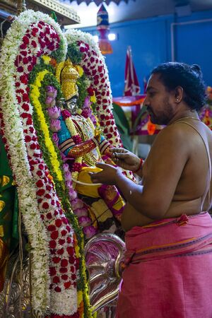 SINGAPORE - FEB 24 : Indian man decorating idol in Sri Veeramakaliamman temple in Little India, Singapore on February 24 2018 It is one of the oldest temples in Singapore.
