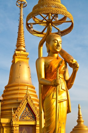 golden pagoda and buddha statue with blue sky, Thailand.