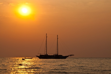 Silhouette of boat in evening light, Thailand. photo