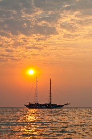 Silhouette of boat in evening light, Thailand.