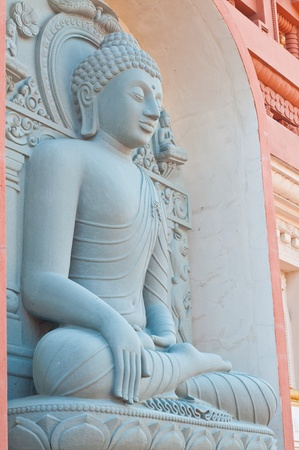 Grey buddha statue on the wall, Thailand.