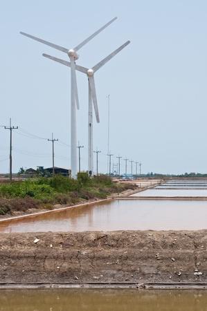 Salt farm and wind turbines generating electricity, Thailand. photo