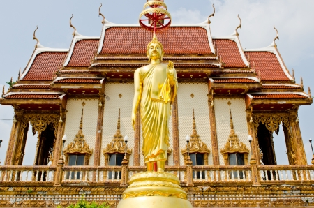 Standing buddha with Thai church background, Thailand. photo
