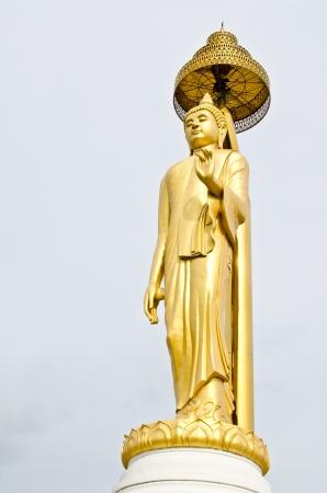 veneration: Golden buddha statue with grey sky, Thailand.