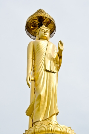 Golden buddha statue with grey sky, Thailand. photo