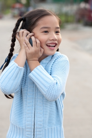 Portrait of the Thai beautiful girl in blue sweater suit, she is calling, Thailand.