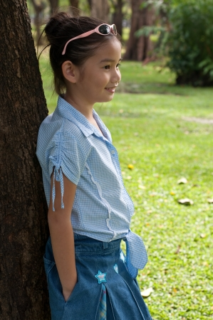 Portrait of beautiful little asian girl in the park, Thailand. photo
