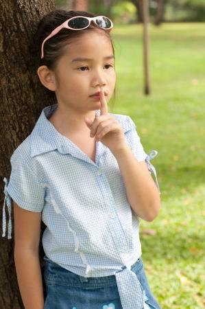 shh: Portrait of beautiful little asian girl in the park,  she make finger on lips, Thailand.